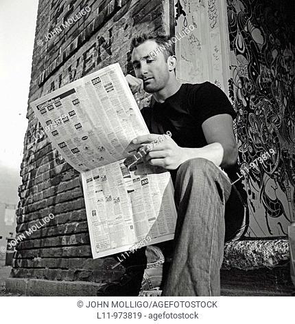 Man seated in doorway, reading a newspaper