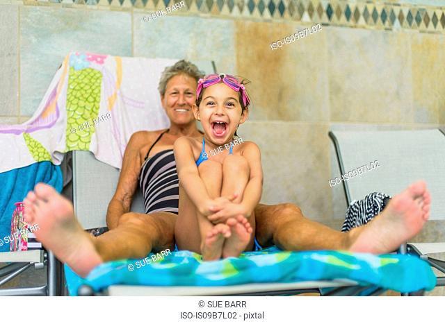 Girl sitting between grandmother's legs on deckchair