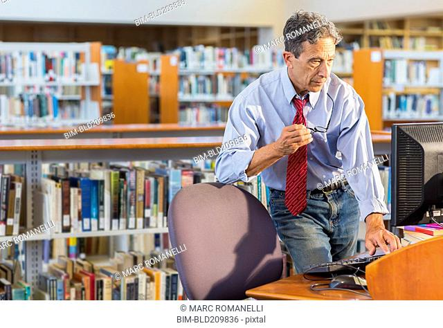 Senior man working at computer in library