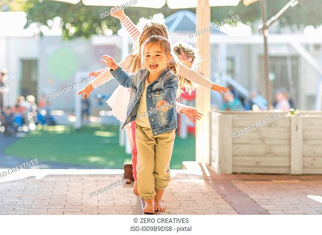 Group of young children, outdoors, walking along balance beam