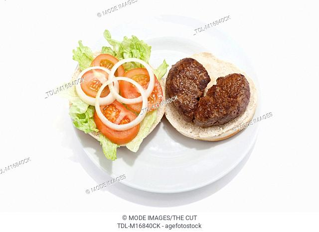 A broken heart shaped beef burger on a bun, with tomato sauce and a side salad