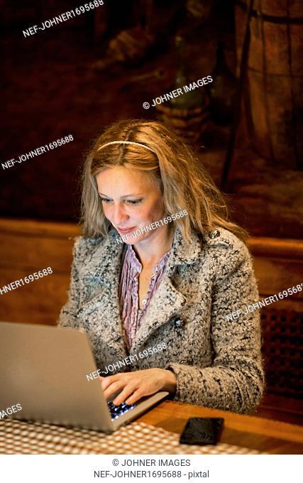 Mature woman using laptop in bar
