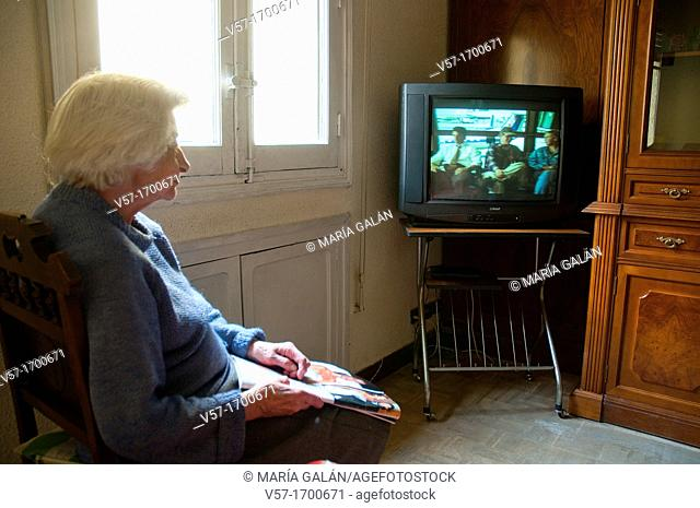 Old woman watching television at her home