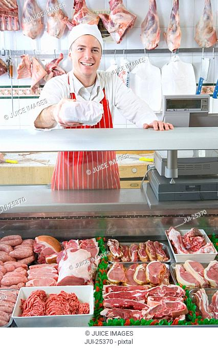 Smiling butcher serving meat from display case