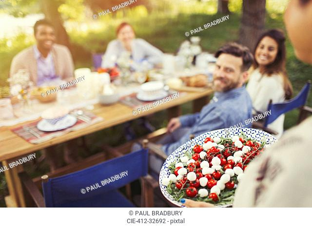 Woman serving Caprese salad appetizer to friends at patio table