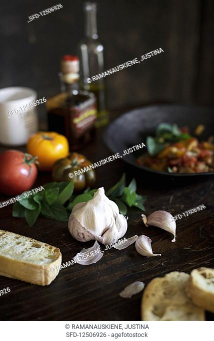 An arrangement of garlic, tomatoes, basil and bread