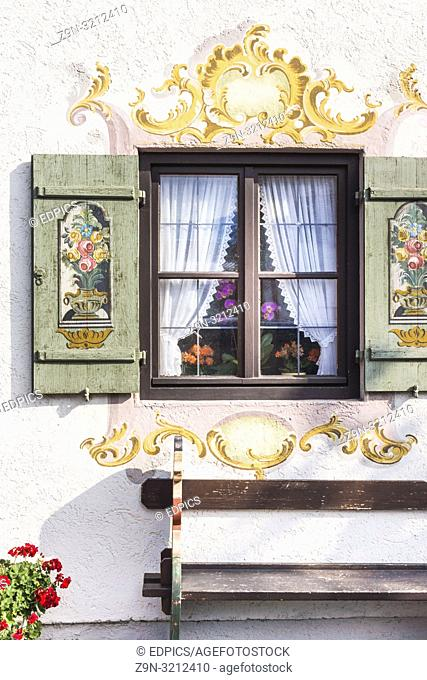 bench under a window with wooden shutters painted with floral motifs, garmisch-partenkirchen, bavaria, germany