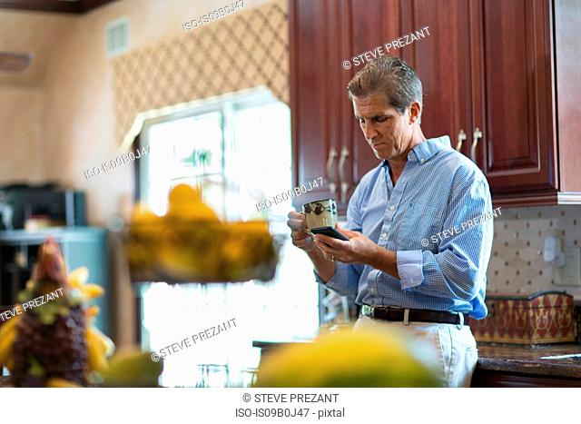 Mature man in kitchen, holding coffee, using smartphone