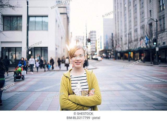 Teenage girl standing with arms crossed in city intersection