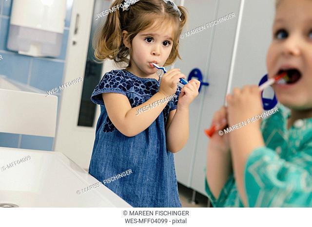 Little girls brushing their teeth in bathroom of a kindergarten