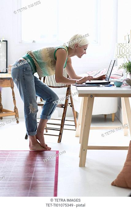 Woman using laptop and at home