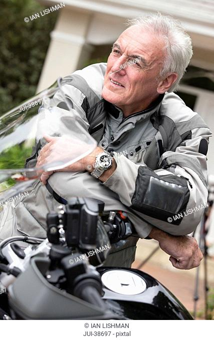 Pensive senior man leaning on motorcycle with arms crossed