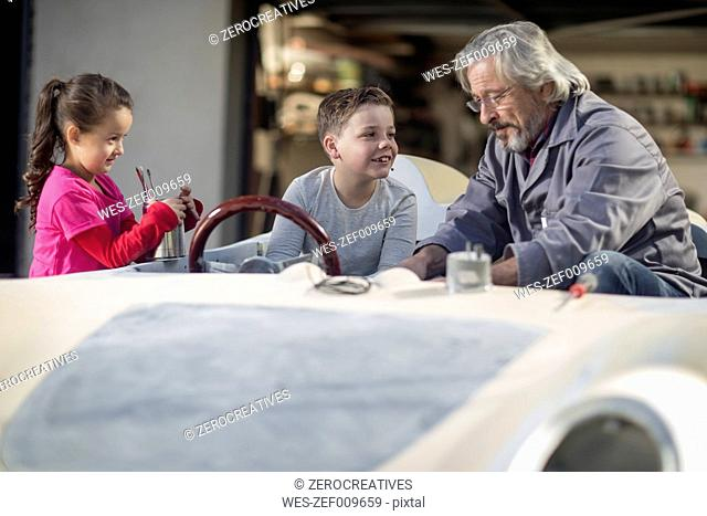 Senior man with boy and girl in a convertible to be restored