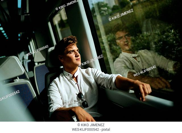Young man looking out of window on a train