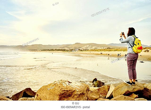 Female tourist photographing sea view on smartphone, Morro Bay, California, USA