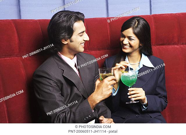 Close-up of a businesswoman and a businessman sitting on a couch and holding glasses