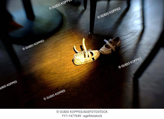 A pair of children's shoes left in a spotlight near the tables of a grand-cafe. Image made with a 'Lensbaby'