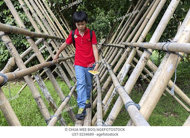 Crossing a bamboo bridge at Sarawak Cultural Village, Damai, Malaysia