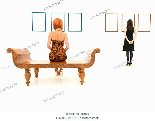 rear view of two women in a white room looking at empty frames displayed on walls in front of them