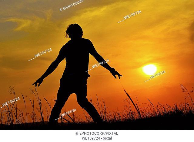 Silhouette of a Hip Hop Dancer posing near mountain at sunset, Pune, Maharashtra