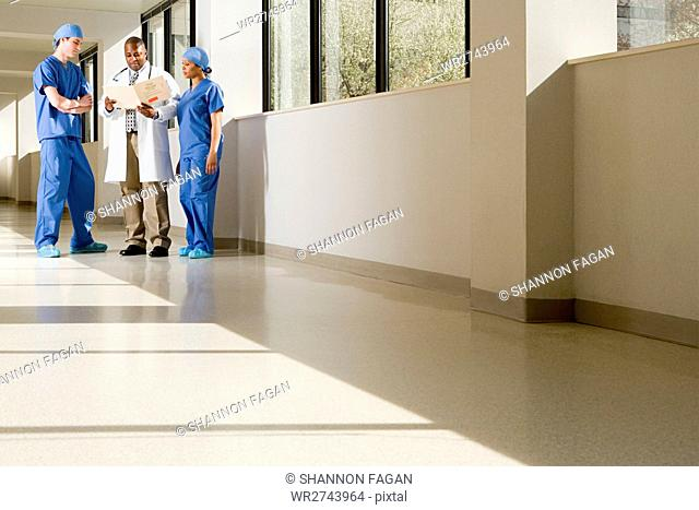 Surgeons and doctor looking at file