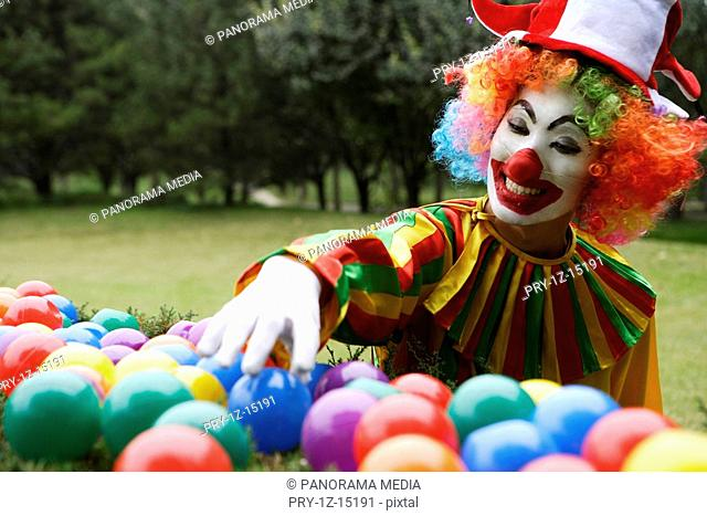 Clown holding ball and smiling