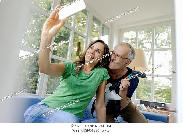 Happy mature couple taking a selfie at home with man playing toy electric guitar