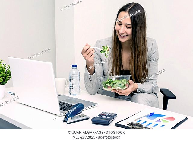 Smiling young woman sitting and eating a salad in coworking space. Horizontal indoors shot