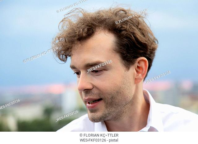 Portrait of relaxed businessman with stubble and curly brown hair