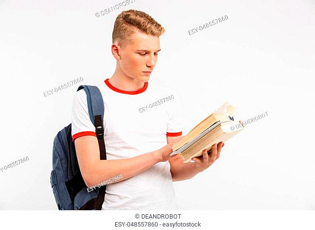 Image of young serious male student wearing backpack studying and reading books with concentration isolated over white background