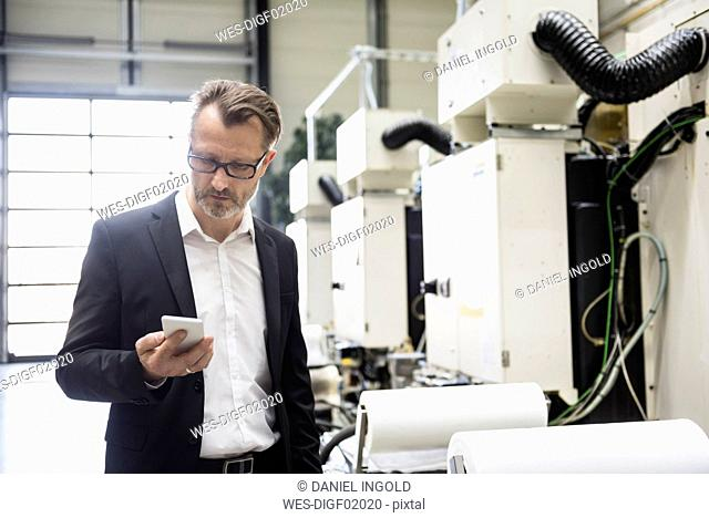 Businessman in factory shop floor looking on the phone
