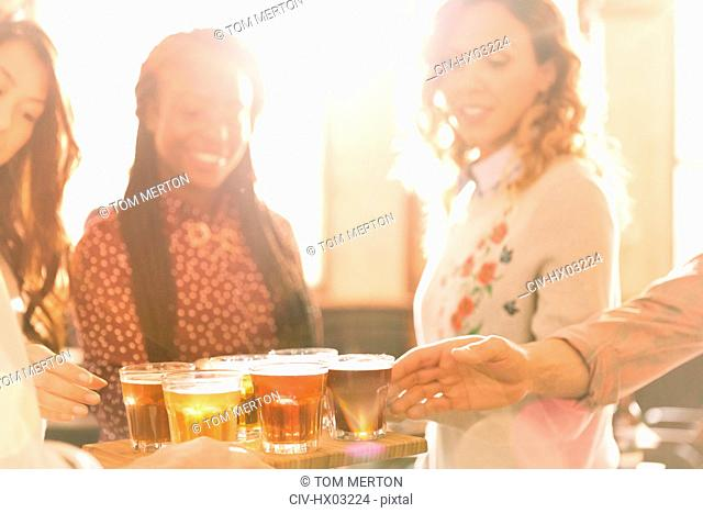 Women friends sampling beer at microbrewery bar