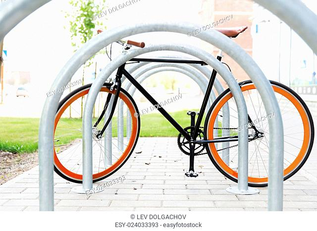 transport, storage and vehicle concept - close up of fixed gear bicycle at street parking outdoors