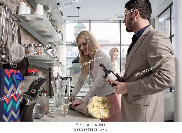 Man and woman with bunch of flowers and wine bottle in kitchen