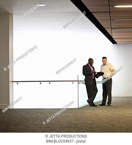 Businessmen talking in office hallway