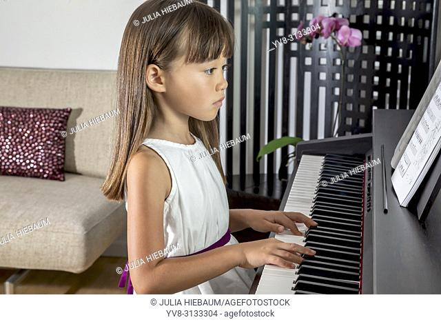 Six year old girl practicing the piano