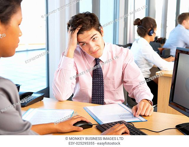Stressed Employee Working In Busy Office