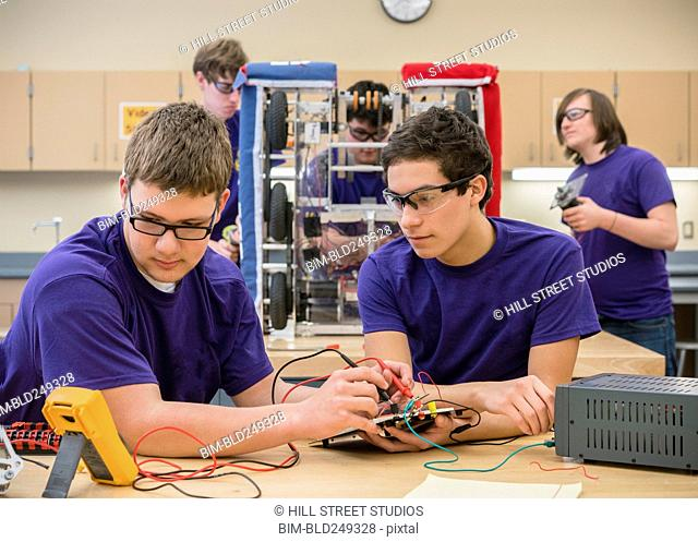 Caucasian boys testing electronics at school