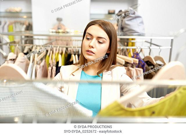 woman choosing clothes at clothing store