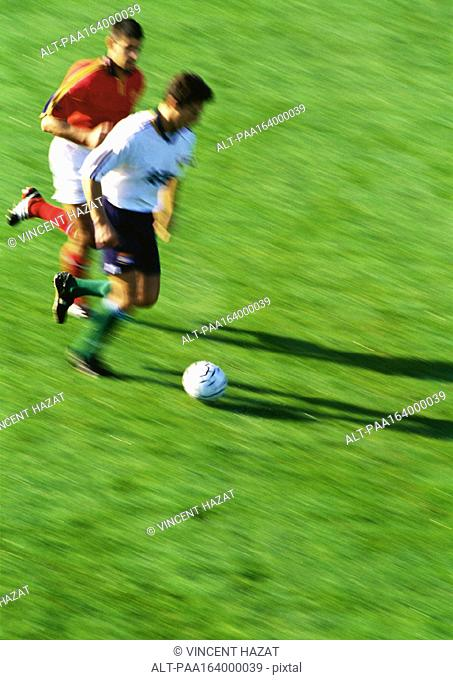 Two soccer players running for ball, blurred