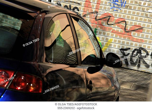 A car parked in the street in front of graffiti wall. Barcelona, Catalonia, Spain