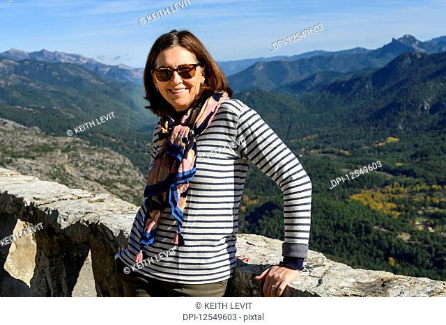 A mature woman stands smiling for the camera with the Sierra de Cazorla mountain range in the background; Cazorla, Jaen Province, Spain