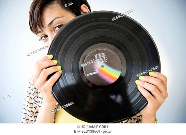 Mixed race woman holding vinyl record