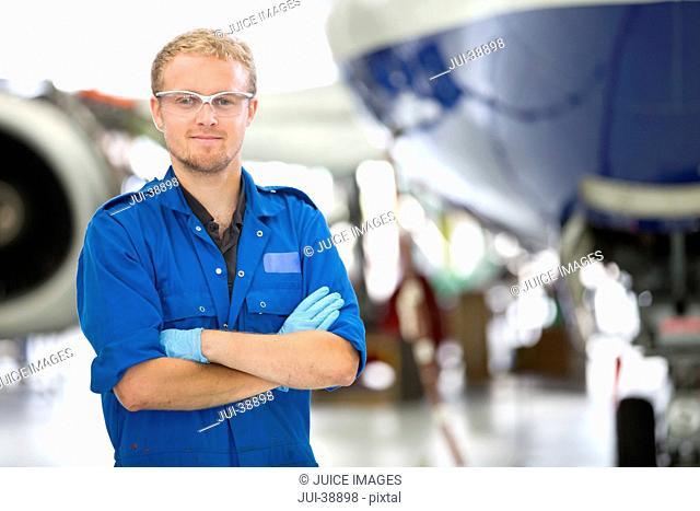 Portrait of confident engineer in front of passenger jet in hangar