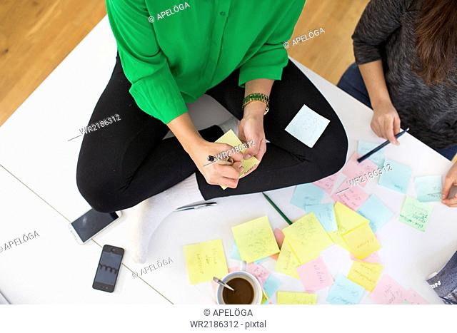 High angle view of businesswomen writing reminders on adhesive notes in office