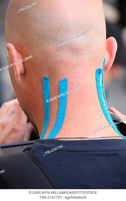 Man wearing blue adhesive medical support strips on neck muscles