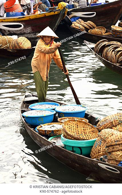 A woman rowing boat full of fish for sale at fishmarket, Hoi An, Vietnam, South East Asia
