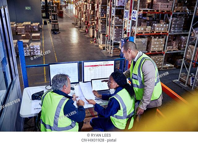 Managers at laptop and computers discussing paperwork in distribution warehouse