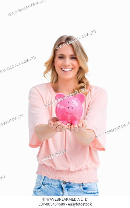 A smiling woman is holding a piggy bank in the palms of her hands