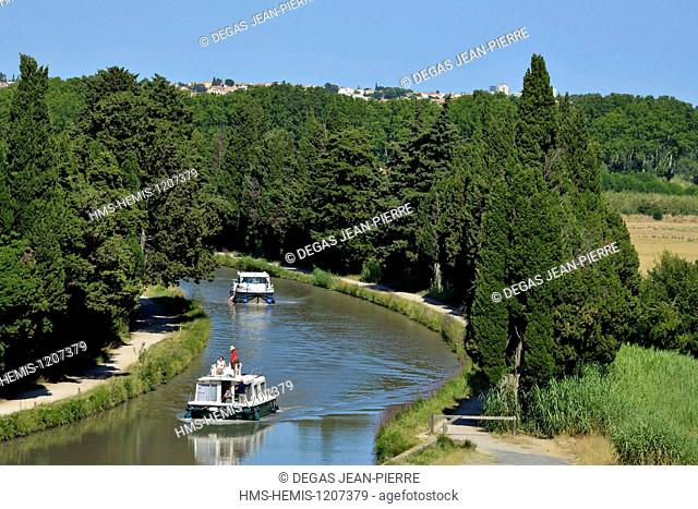 France, Herault, Beziers, Canal du Midi listed as World Heritage by UNESCO, pleasure boats downstream to the locks of Fonseranes in the middle of cypress